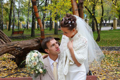 Bride and groom look at each other in autumn park Stock Images