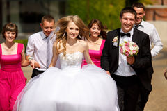 Bride and groom look happy walking in the park with friends Stock Photo