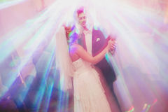 Bride and groom look like the angels dancing in the bright rays. Of disco lights Stock Photography