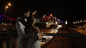 Bride and groom look at the night city. stock video footage