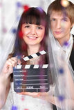 Bride and groom look; woman holds clapper board. Happy beautiful bride and groom look at camera behind transparent curtain of beads; women holds clapper board Royalty Free Stock Image