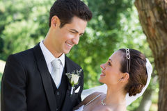 Bride and groom looking at each other in garden Royalty Free Stock Image