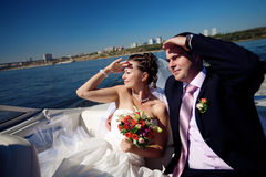 Bride and groom looking forward on the boat Royalty Free Stock Image