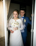 Bride and groom looking out of hotel room window Royalty Free Stock Photo