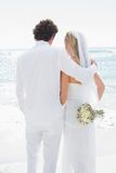 Bride and groom looking out to sea embracing Royalty Free Stock Photos