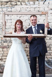 Bride and groom looking through portrait frame Stock Image