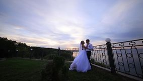 Bride and groom are looking at sunset from a balcony in a park. With FlyCam stock video footage