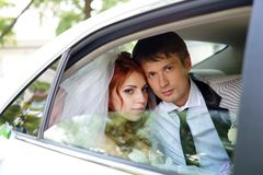 Bride and groom. The bride looks out of a car window royalty free stock photography