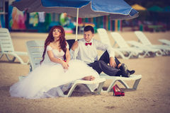 Bride and groom on a lounger. Newlyweds on the beach sitting on a deck chair. Bridal bouquet with a red ribbon, the groom with a red bow tie. Red-haired Bride royalty free stock photo