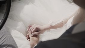 Bride and groom in love sitting on a car, holding hands and talking with each others. stock footage