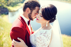 Bride and groom, lovely couple, cuddling on waterfront, photo shoot after wedding ceremony. Stylish man with mustache. Bride and groom, lovely couple, cuddling stock photography