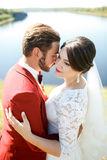 Bride and groom, lovely couple outdoor, river in background. Royalty Free Stock Images