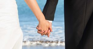 Bride and groom lower bodies holding hands against blurry beach shore. Digital composite of Bride and groom lower bodies holding hands against blurry beach shore Royalty Free Stock Photography