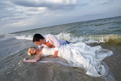 Wedding on beach. Bride and Groom lying in beach shore Stock Photo