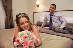 Bride and groom lying on bed Royalty Free Stock Image