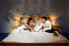 Bride and groom lying on bed Royalty Free Stock Images