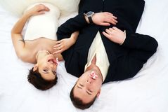 Bride and groom lying in bedroom with orchids Royalty Free Stock Photography