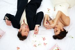 Bride and groom lying in bedroom with orchids Royalty Free Stock Image