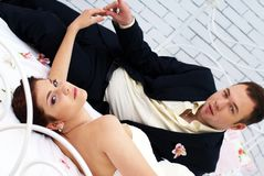 Bride and groom lying in bedroom with orchids Stock Photography