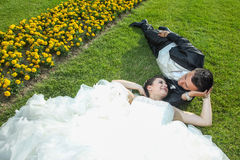 Bride and groom lying down on lawn with flowers Royalty Free Stock Image