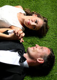Bride and groom lying on the grass while holding each other hand Stock Photography
