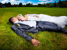 Bride and groom lying on grass at park Stock Image
