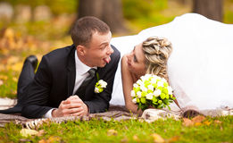 Bride and groom lying on grass at park and making funny faces Royalty Free Stock Image