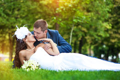 Bride and groom are lying on green grass Royalty Free Stock Image