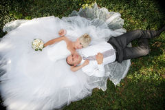 Bride and groom lying on green grass Royalty Free Stock Image