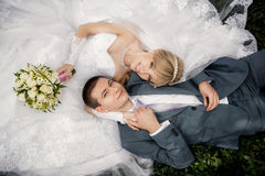 bride and groom are lying on green grass Royalty Free Stock Photos