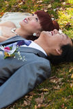 Bride and groom lying on ground Royalty Free Stock Images