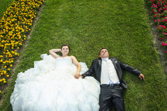 Bride and groom lying on lawn with flowers Stock Photo