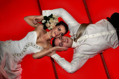 Bride and groom lying on red floor Stock Images