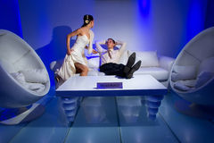 Bride and groom lying in a stylish lounge Stock Photography