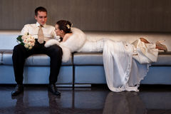 Bride and groom lying in a stylish lounge Stock Images
