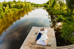 Bride and groom lying on a wooden pier near the pond Stock Photos