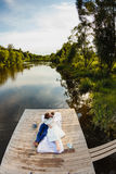 Bride and groom lying on a wooden pier near the pond Royalty Free Stock Photo