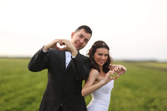 Bride and groom making love sign Stock Photo