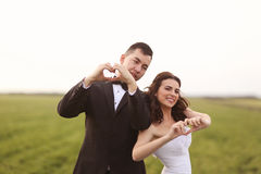 Bride and groom making love sign Stock Images
