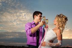 Bride and groom making at sunset Stock Photography
