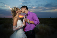 Bride and groom making at sunset Stock Photo