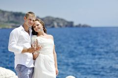 Bride and groom making a toast by the sea in wedding day Stock Photos