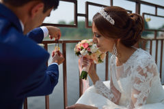 Bride and groom makingt the tradition at weddings hanging the lock on the bridge Royalty Free Stock Image