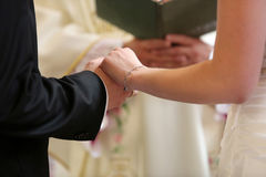 Bride and groom during the marriage oath. Holding hands together Royalty Free Stock Image