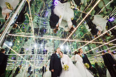Bride and groom in mirrored room, mirror labyrinth Royalty Free Stock Image