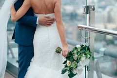 Bride and groom in the morning standing on the balcony overlookin the city stock photo