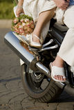 Bride and groom on motorbike. A bride and groom on the back of a motorbike Stock Photography