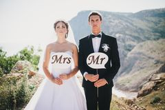 Bride and groom with Mr and Mrs signs. Just married beautiful young bride and groom standing with Mr and Mrs signs on the mountains background stock photos