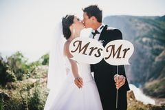 Bride and groom with Mr and Mrs signs. Just married beautiful young bride and groom standing with Mr and Mrs signs on the mountains background royalty free stock photography