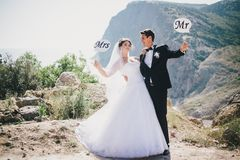 Bride and groom with Mr and Mrs signs. Just married beautiful young bride and groom standing with Mr and Mrs signs on the mountains background stock photography